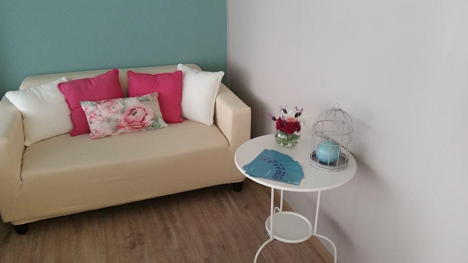 un divano color pesca con dei cuscini e  un tavolino con un vaso di fiori e delle brochure