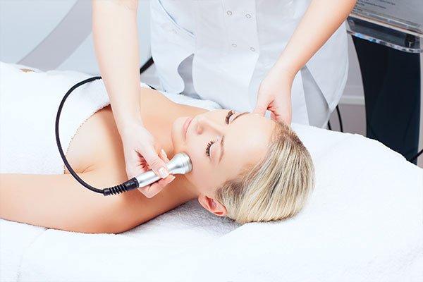 una donna sdraiata su un lettino e un estetista che usa un dispositivo di epilazione sul viso della prima
