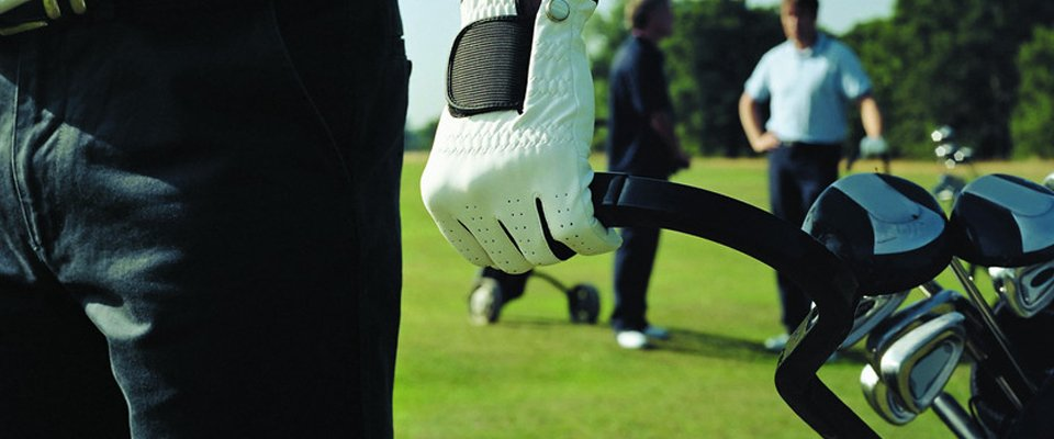 gloved hand pulling golf trolley
