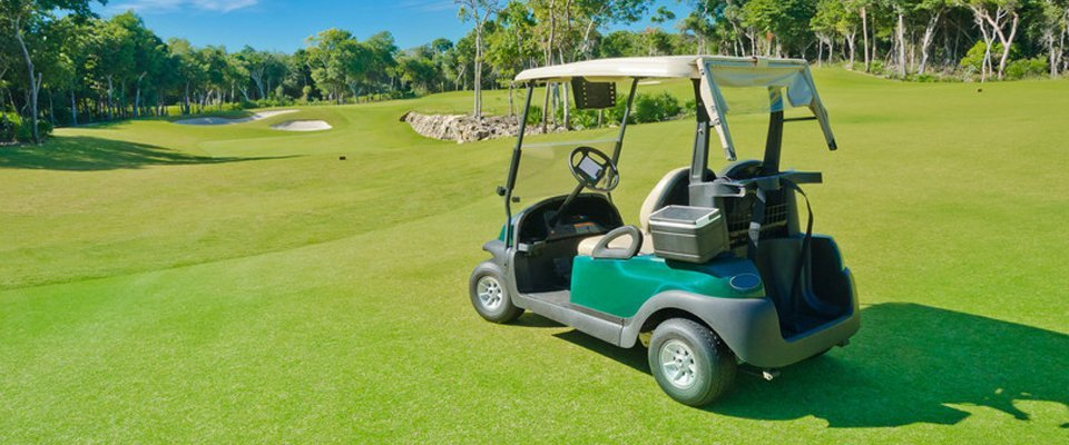 green golf buggy on sunny course