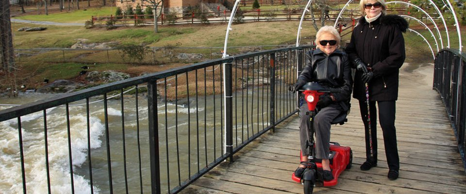 small red mobility scooter crossing wooden footbridge