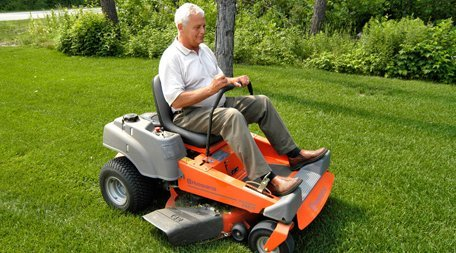 grass cutting with orange and grey ride on mower