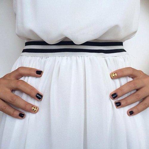 Mani con smalto nero sulle unghie e glitter sull'anulare
