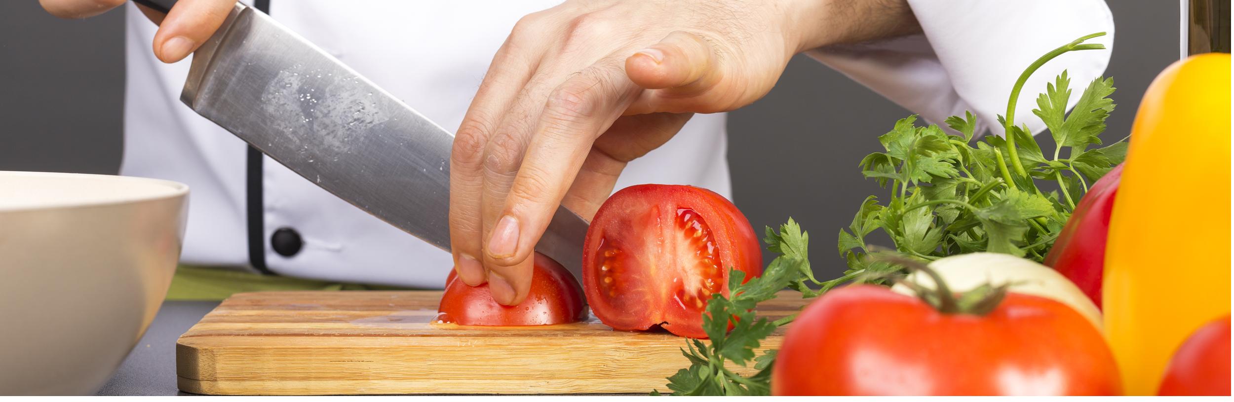 persona mentre taglia dei pomodori su un tagliere