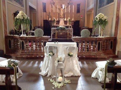 un tavolo e due sedie decorate con dei fiori bianchi all'interno di una chiesa