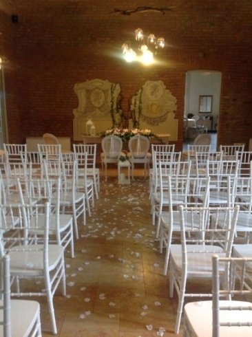 due poltrone bianche, davanti delle sedie e dei petali bianchi sul pavimento