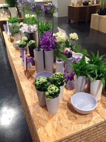 un tavolo con dei vasi grigi con piante fiorite di color blu e viola