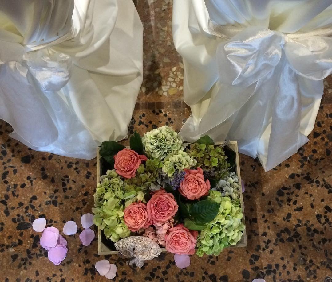 una cassetta di legno con delle orchidee e rose di color arancione