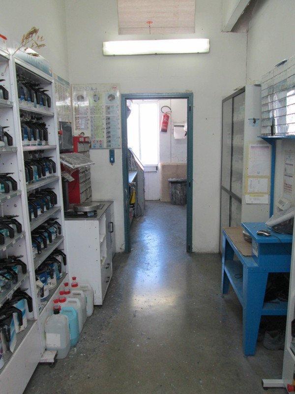 un corridoio con un tavolino azzurro e uno scaffale con delle bottiglie di olio per motori