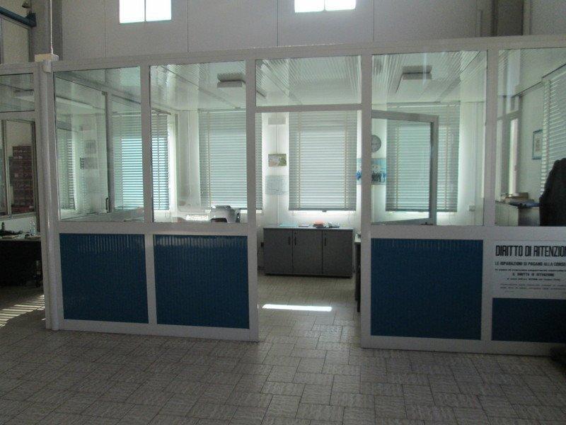 l'ufficio con delle vetrate e delle tende all'interno di una carrozzeria