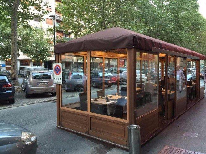 dei tavoli all'esterno in una struttura di legno e vetri
