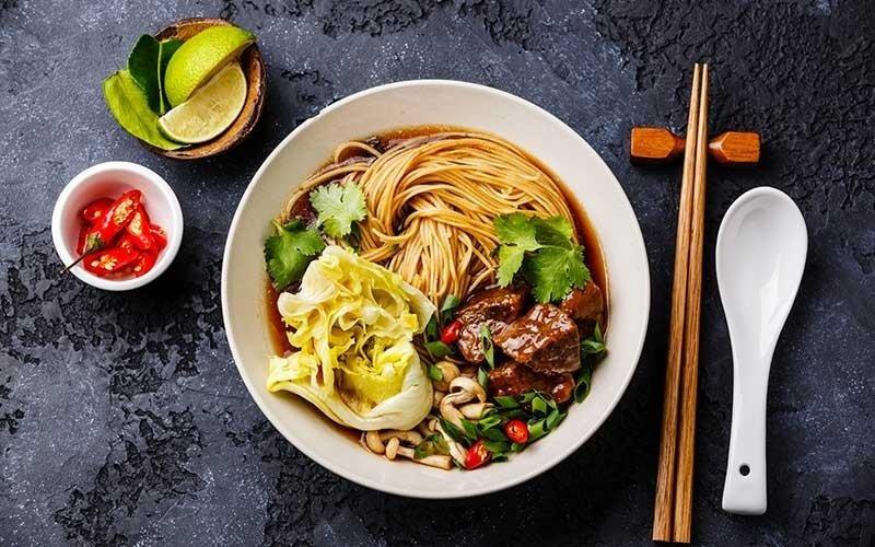 una ciotola con noodles, carne e insalata
