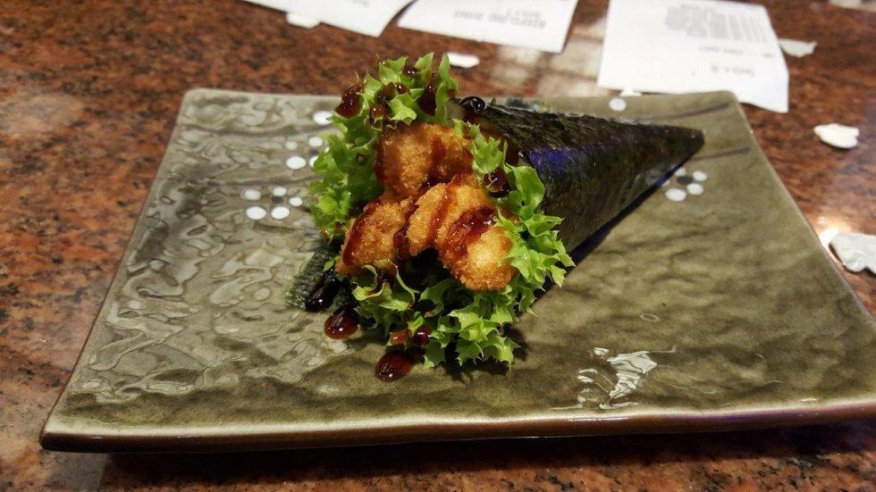 sushi con sopra insalata e pesce fritto