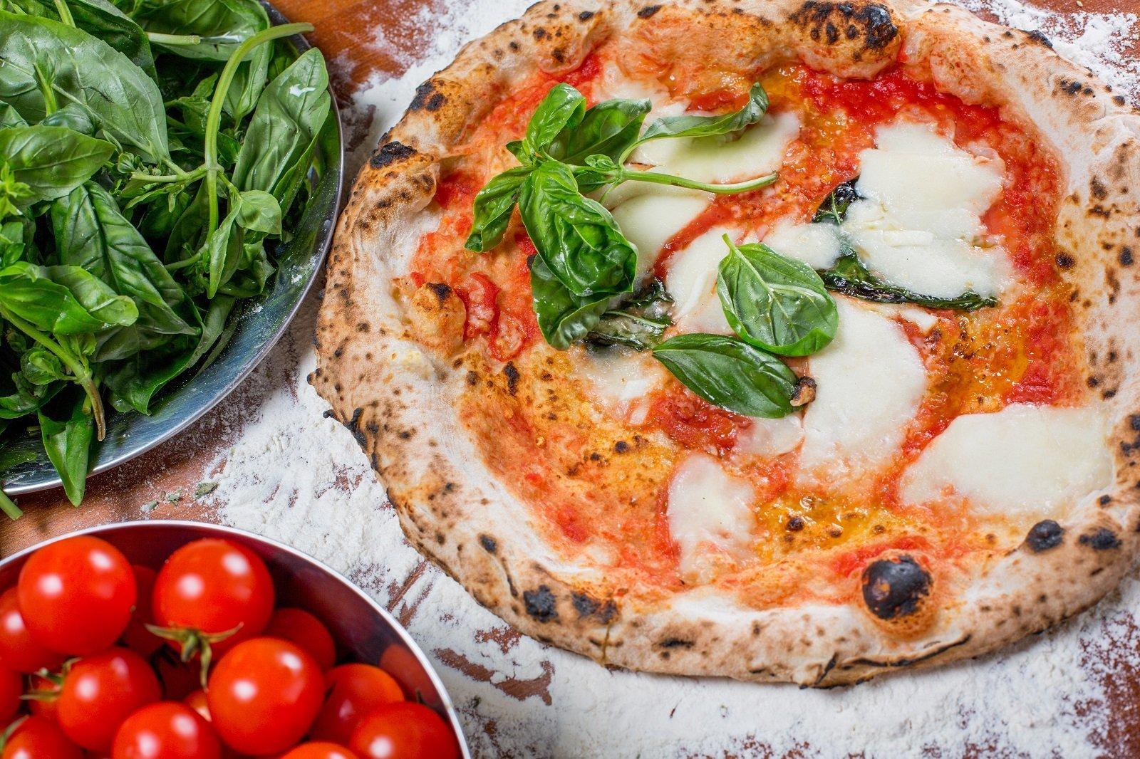 Pizza italiana tradizionale con mozzarella, pomodoro e basilico, su un tavolo in legno con gli ingredienti
