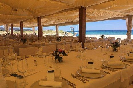tavoli apparecchiati sotto un gazebo fronte mare per un evento speciale