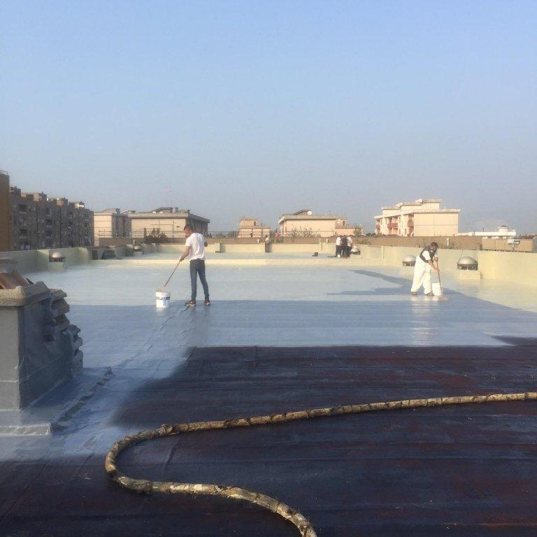degli uomini al lavoro su un ampio tetto