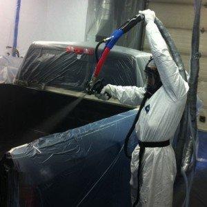un uomo con una tuta protettiva che spruzza dell'acqua nel rimorchio di un pick up