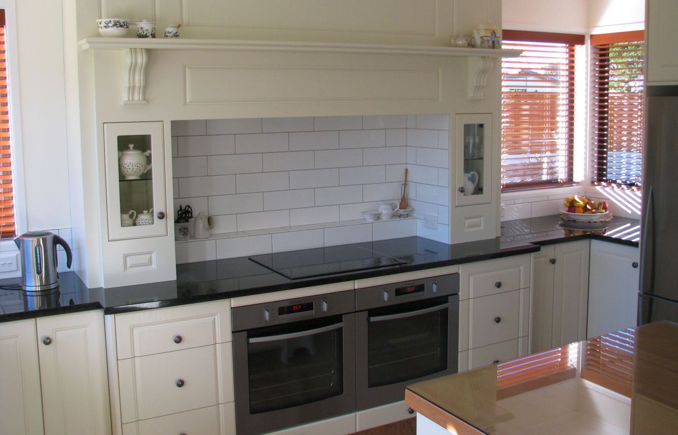 A white kitchen with two ovens