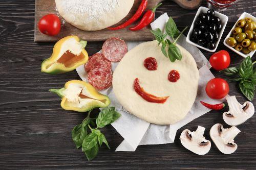una base di una una pizza e accanto delle verdure e delle olive