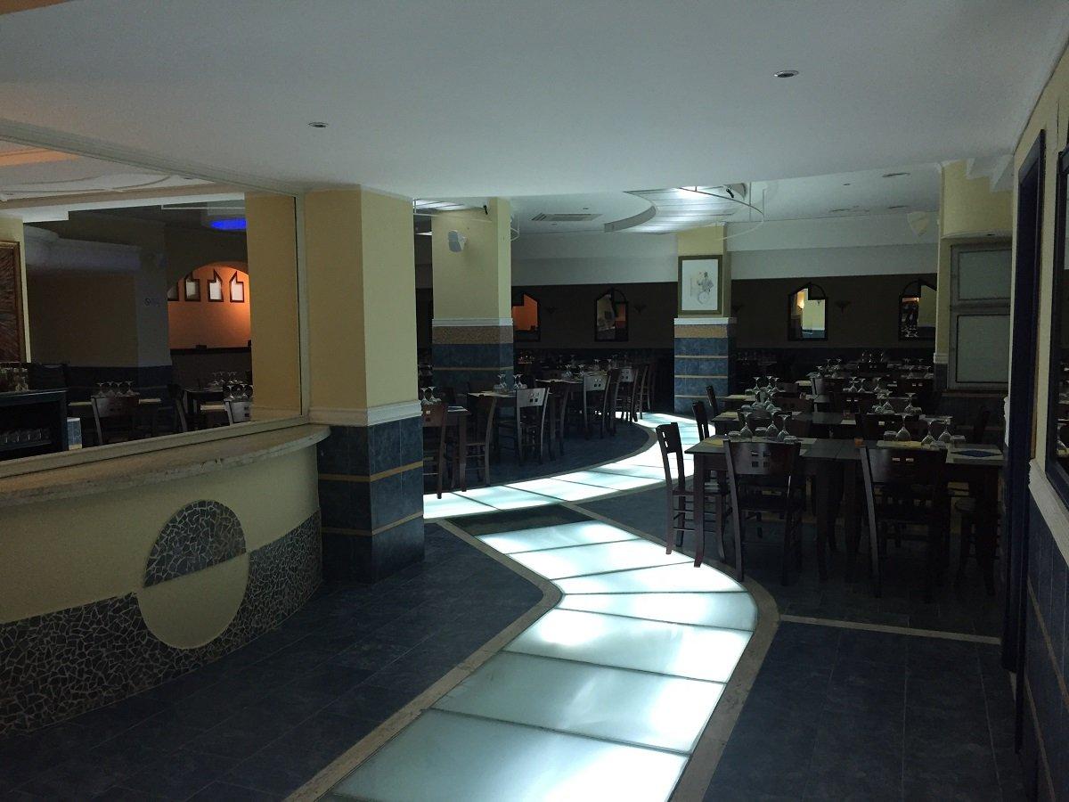 dei tavoli e delle sedie in un ristorante con pavimento del corridoio illuminato