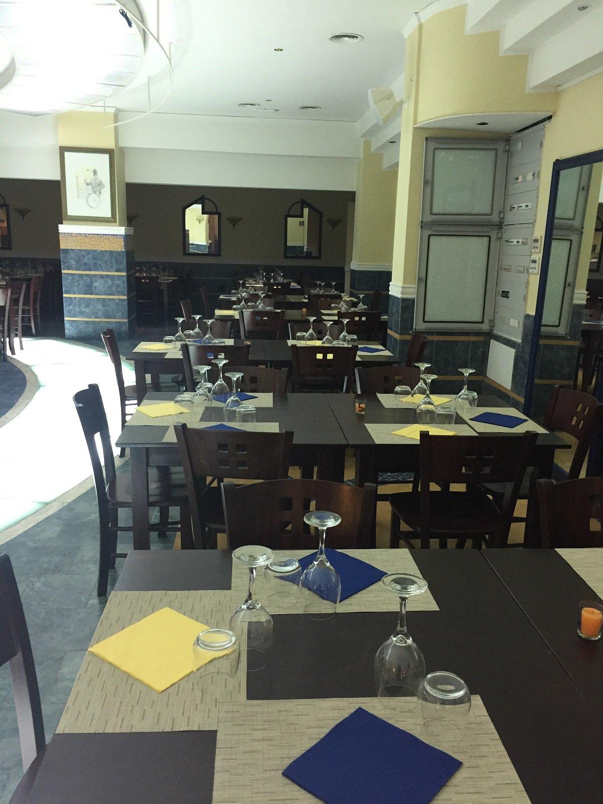 dei tavoli apparecchiati con tovagliette gialle e tovaglioli blu