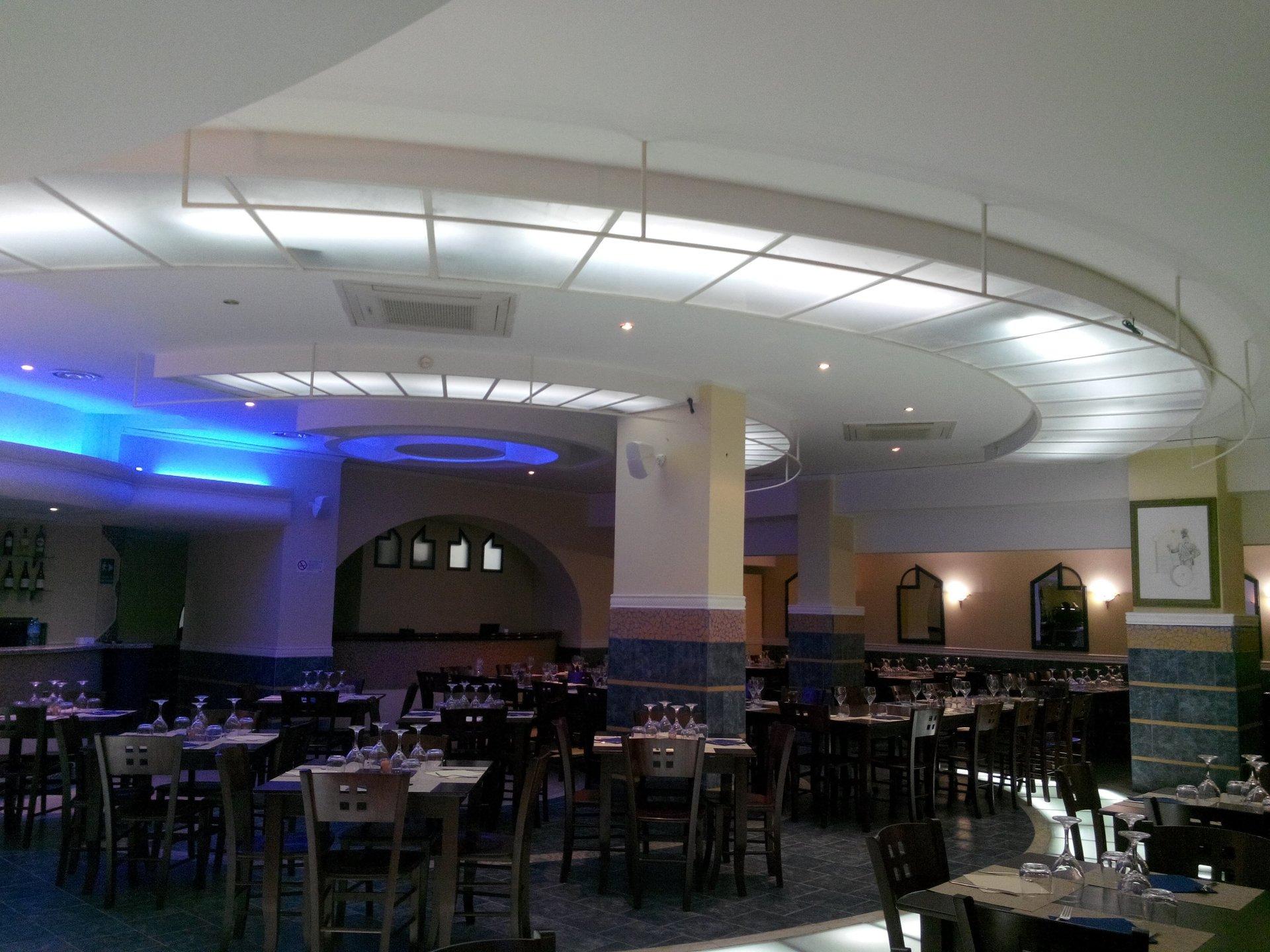 dei tavoli , sedie  e soffitto illuminato in un ristorante