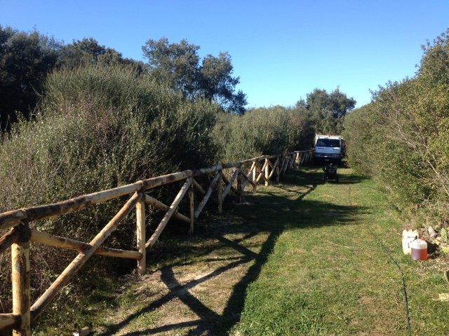 uno steccato in  legno in un prato, alberi su entrambi i lati e un camion bianco in fondo