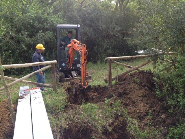 un uomo al lavoro su una scavatrice e accanto un altro con un elmetto giallo