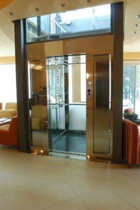 un ascensore con le porte automatiche e accanto dei divani