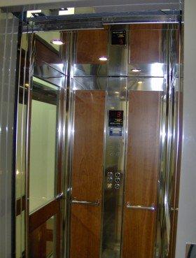 interno di un ascensore con pannelli in acciaio e legno