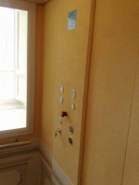 interno di un ascensore con una maniglia dorata