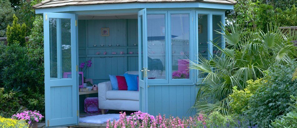 Blue summer house in the garden with doors open to reveal a sofa