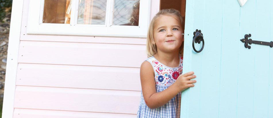White wooden play house with a girl in the door way