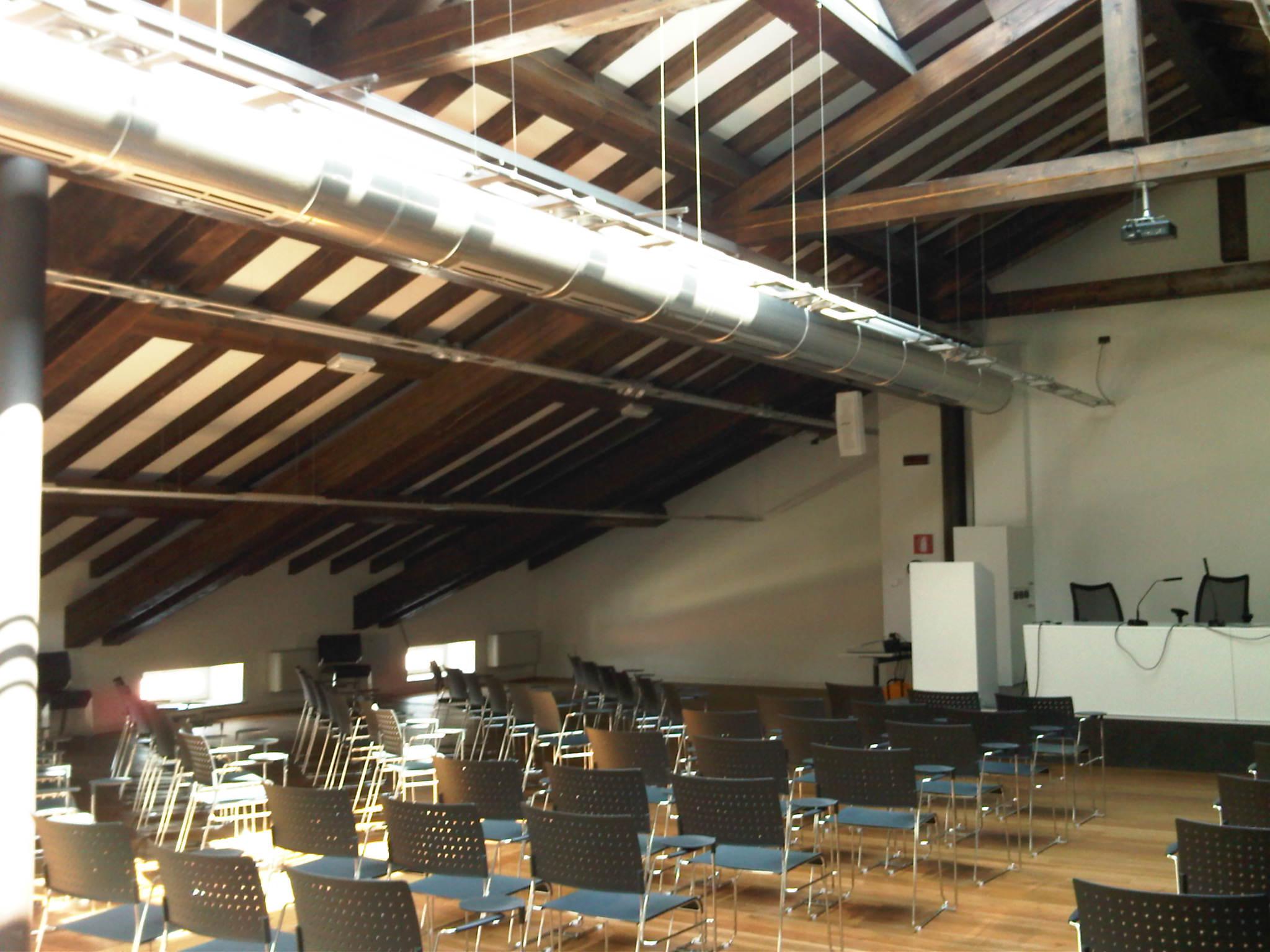 una sala conferenze con delle sedie nere e sopra dei condotti di un impianto