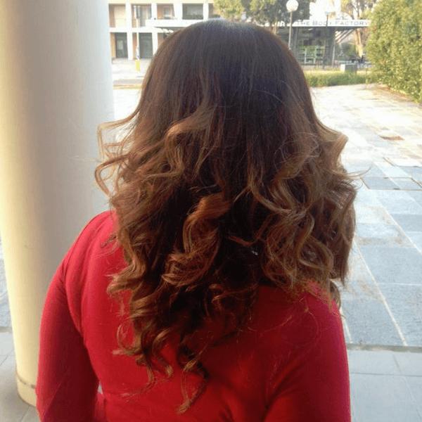 una donna vista di spalle con i capelli castani chiari e che indossa un maglione rosso mentre e' in strada