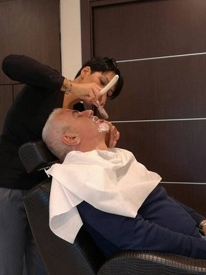 una parrucchiera sta radendo un uomo con pizzetto e capelli bianchi con la faccia rivolta verso l'alto