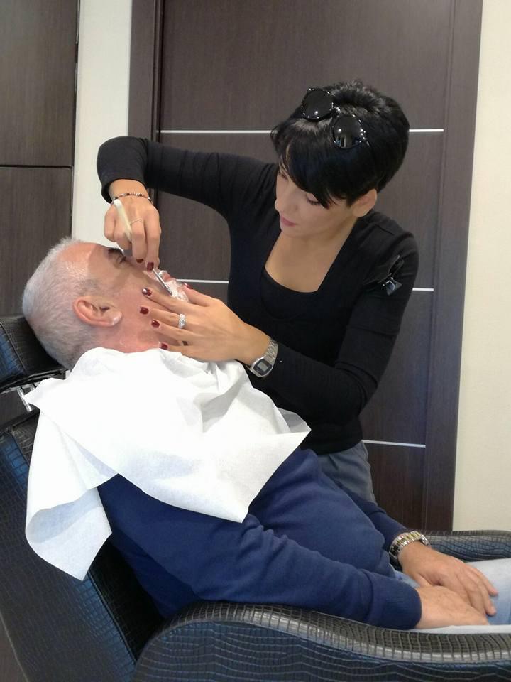 una parrucchiera sta facendo la barba a un uomo