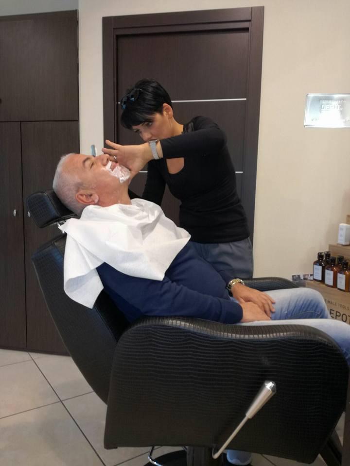 un uomo si sta facendo radere la barba da una parrucchiera