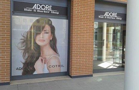 vista delle vetrine del parrucchiere con l'immagine di una donna con capelli neri lunghi e la scritta Adore
