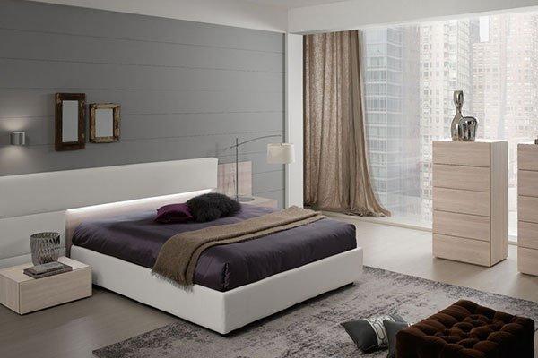Una camera con letto di color crema al centro due comodini e due como di color pino chiaro  e una lampada sopra il comodino destro