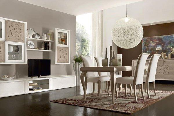 Una sala da pranzo con tavolo e quattro portoncini, una lampada a sospensione a forma di palla grande di color bianco, un mobile tv e un buffet