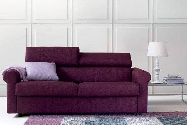 Un divano a tre posti di color viola e un cuscino di color lilla, sulla destra un tavolino con una lampada e un tappeto davanti al divano