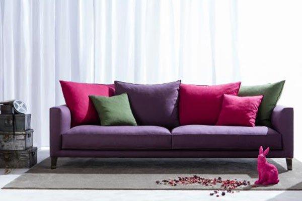 Un divano di color viola con dei cuscini di color fucsia, viola e verde e davanti una statuetta di un coniglio viola con dei potpourri