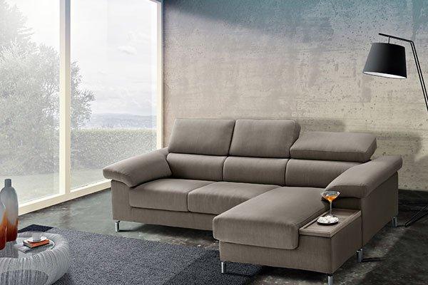 un divano angolare color beige sulla destra una lampada da terra nera e di fronte un tavolino di cristallo con sopra degli oggetti
