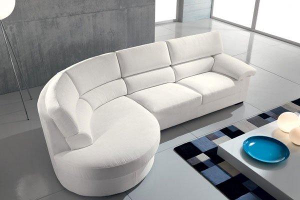 un divano angolare color panna  e di fronte un tavolino con sopra un piatto azzurro e altri oggetti