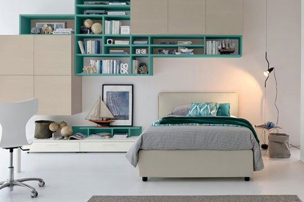 una camera da letto con uno scaffale mensola color verde smeraldo a scompartimenti con sopra degli oggetti, sotto un letto, una lampada sulla destra e sulla sinistra un comodino con sopra un modellino di una barca a vela