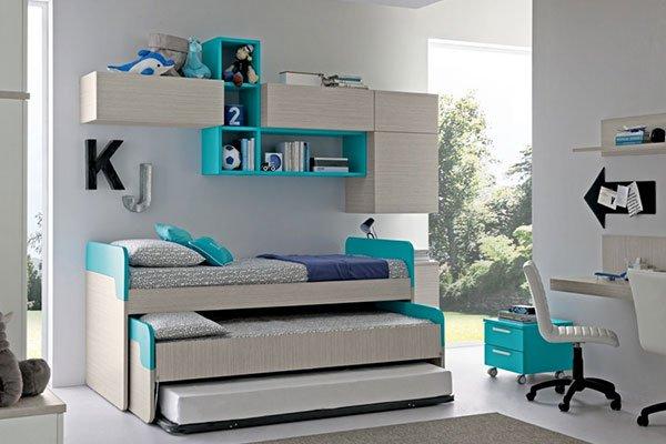 camera da letto con armadietti a muro color beige e mensole verde smeraldo con sopra degli oggetti, sotto tre letti a cassetto e sulla destra una scrivania con una sedia bianca