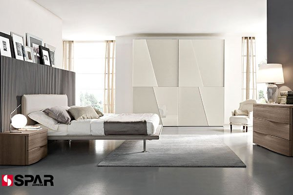 camera da letto moderna con sulla sinistra un letto con un comodino, in mezzo un armadio bianco e sulla destra un comò in legno con sopra una lampada