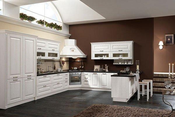 una cucina in legno bianco angolare con penisola e arredamento completamente bianco