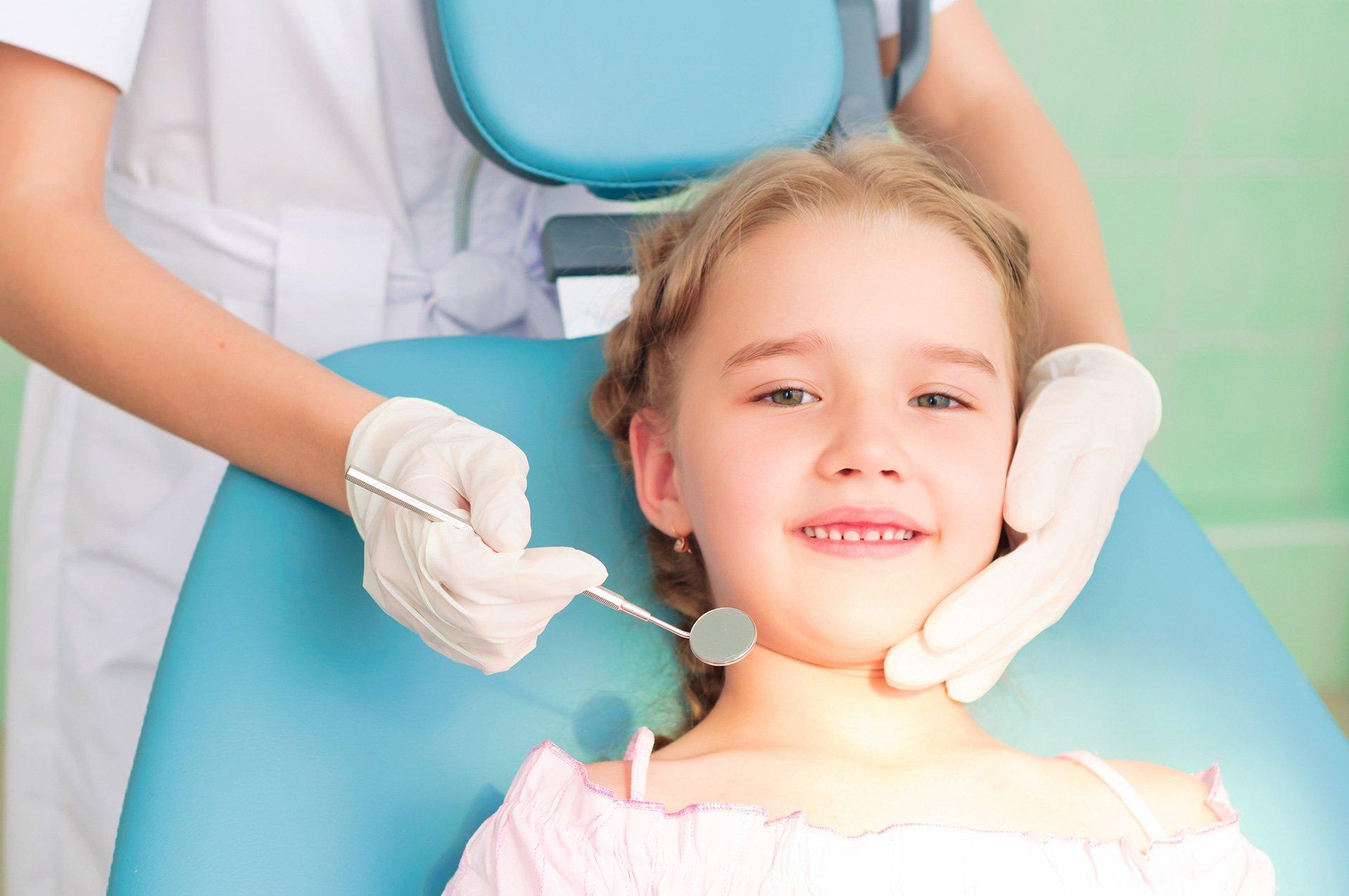 Bambina sorride sul lettino da dentista
